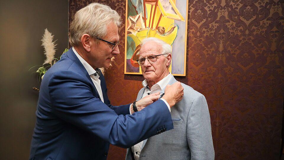 Wethouder Dirk Kuipers speldt de waarderingsspeld bij meneer Hoogland op zijn jasje.